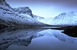 Snow-covered mountains and reflections in loch, Scotland