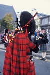 Highland Piper showing red tartan cape